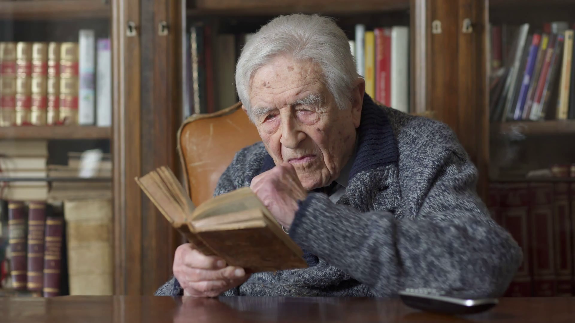 videoblocks-portrait-of-very-old-man-reading-a-book-sitting-at-the-desk_hr6hdtv0e_thumbnail-full01